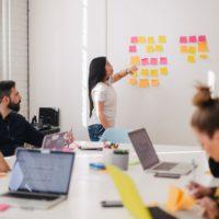 Bild Forschendes Lernen, mehrere Lernende in einen Raum mit Laptops und einer Person vor einem Whiteboard mit Post-It-Zetteln
