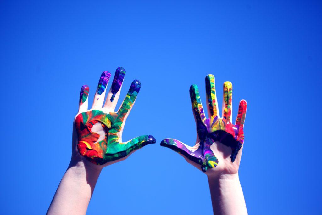 In bunte Farbe getauchte Handflächen vor blauem Himmel
